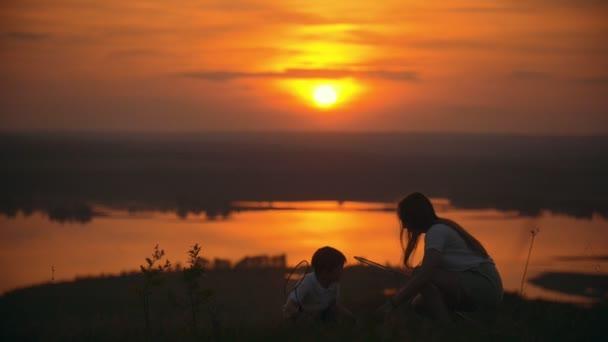 Malý chlapec hraje badminton a bavit se svou starší sestrou na kopci při západu slunce