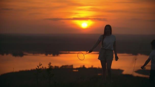 Mladá žena volá dítě hrát badminton na kopci při západu slunce vřít
