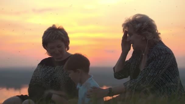 Šťastná rodina - babička, matka a syn sedí na vysokém kopci u letní západ slunce