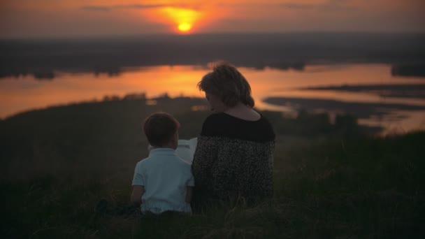 Madre con il figlio che si siedono sulla collina leggendo un libro al tramonto di estate