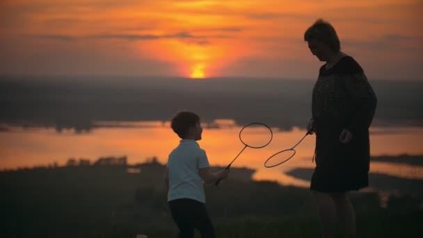 Matka se svým malým synem hraje badminton na kopci při západu slunce