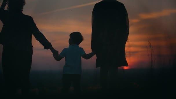 Madre e la nonna con il piccolo figlio che cammina sul campo estivo che tengono le mani al tramonto