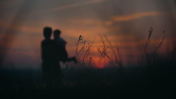 Siluette della madre con il piccolo figlio divertirsi al tramonto di estate attraverso lerba