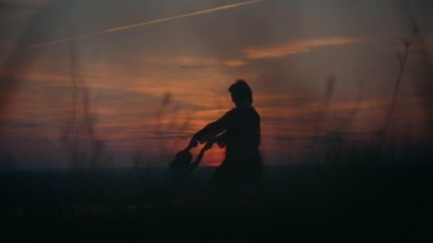 Siluette della madre con il suo piccolo figlio divertirsi al campo di estate sul tramonto, primi piani