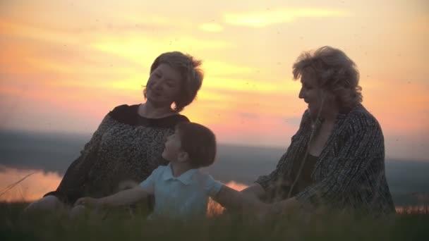 Madre, nonna con il piccolo figlio seduto sullerba schiacciando alle zanzare e parlando al tramonto