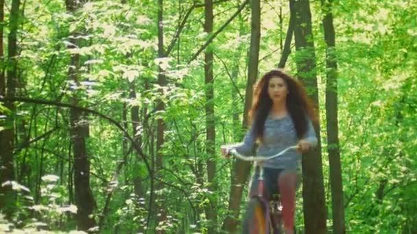 Cyklista brunetka jezdí na kole na pozadí zelených stromů, slunečný den