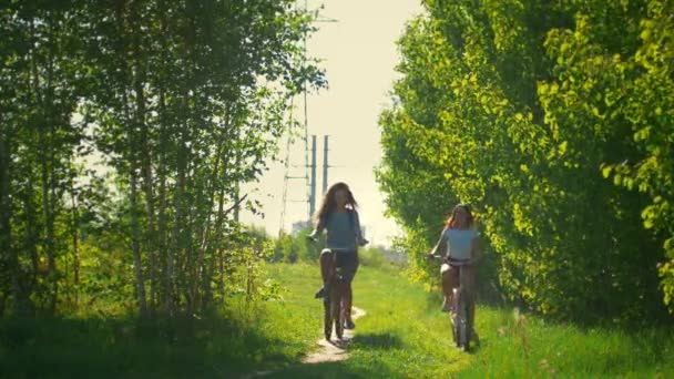 Young girls come on bicycles to the forest to walk