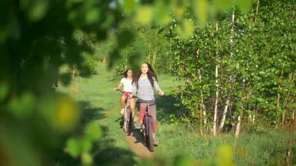 Young cyclists on a summer walk passing by the bushes and smile