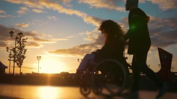 fürsorglicher Mann mit einer behinderten Frau im Rollstuhl, die bei Sonnenuntergang über den Kai läuft