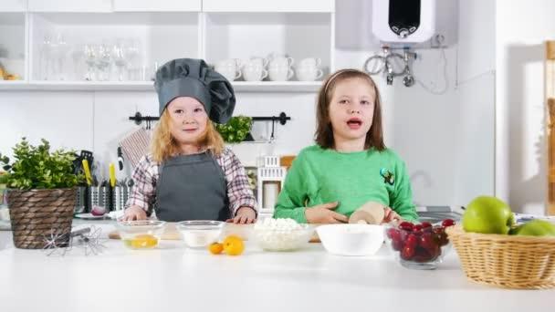 Zwei kindergarten kleine mädchen bäcker winken hände in die kamera