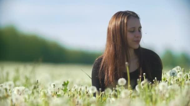 Junge Frau bläst Löwenzahn in einem Sommer Tag im freien