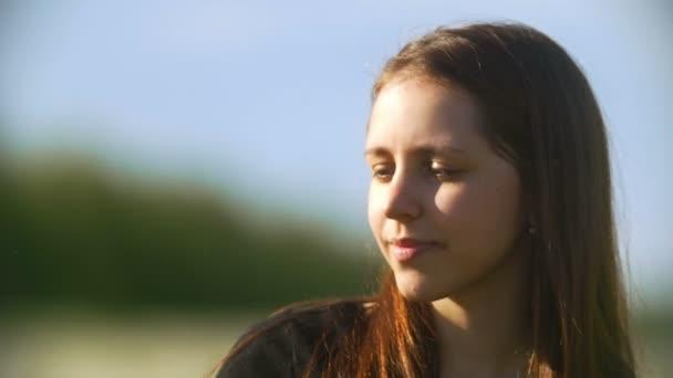 Porträt der jungen Frau bläst Löwenzahn an einem Sommertag in der Natur