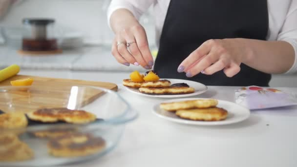 Female hands decorating prepared with their own hands pancakes with fruits and berries