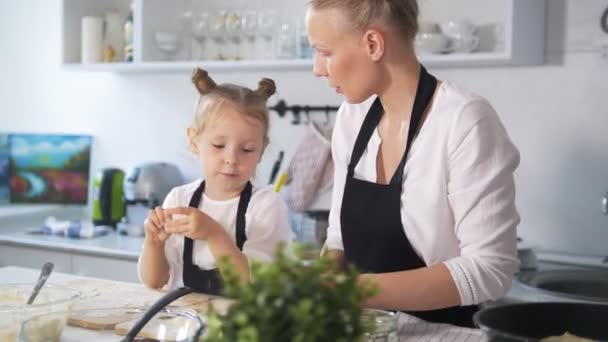 Little caucasian girl with her mother cooking together in the kitchen