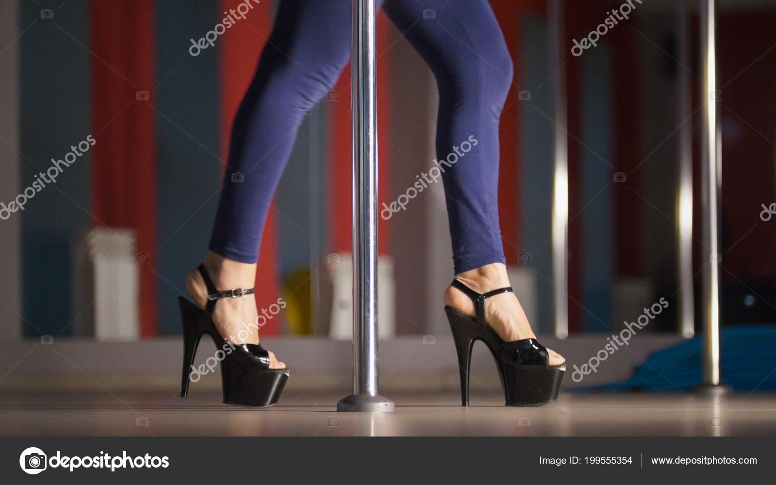 9d6dfedafb3 Belles jambes de femme en chaussures à talons hauts noirs danse sur un  poteau dans un studio