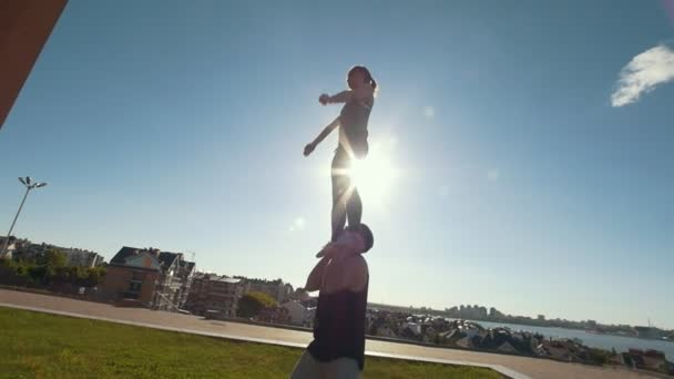 Young couple practicing acrobatics performing front plank bird pose, young man raises flying young woman balancing on his arms at sunset