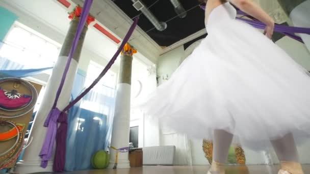 Půvabná tanečnice v bílých šatech provádí tanec v prostorné studio bílá