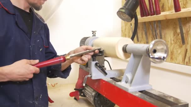 Young man in protective mask makes woodworking of joinery using hand screwdriver in workshop
