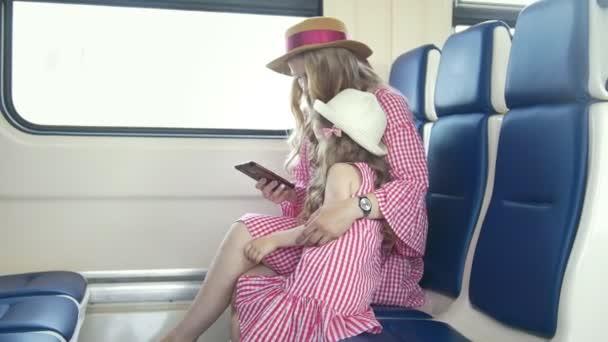 Mladý bělošský máma a dcera v náručí jízda vlaku a pomocí mobilního telefonu