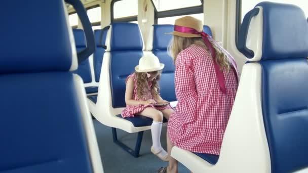 Malá holčička použijte smartphone a seděli v přední části její matka ve vlaku
