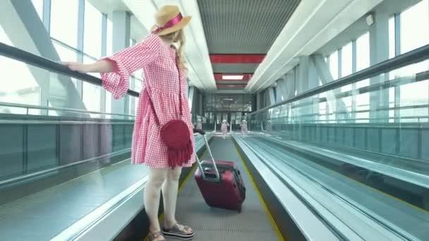 Rückansicht von Mutter und kleiner Tochter auf der Rolltreppe am Flughafen