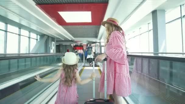 Zadní pohled na matku a malá dcerka, drželi se za ruce do čekárny v Letiště