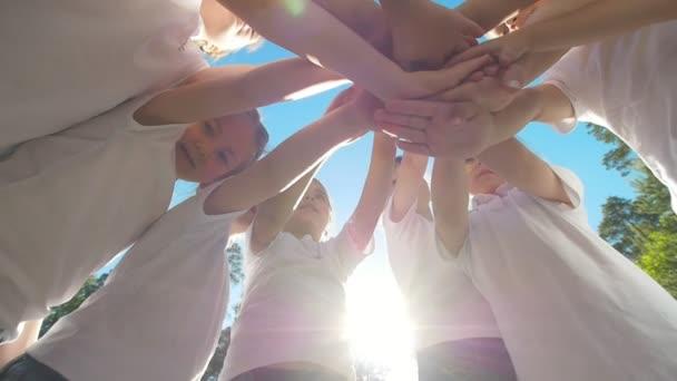Skupina dětí provádí sportovní motivační pozdrav s rukou na hřiště fotbal dvůr na slunečný den
