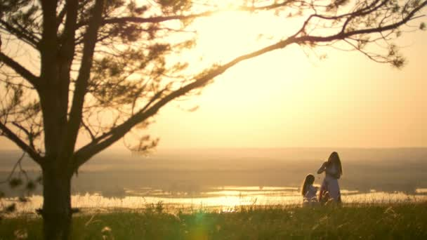 Young mother weaves a wreath for little daughter under the large tree on the hill at sunset