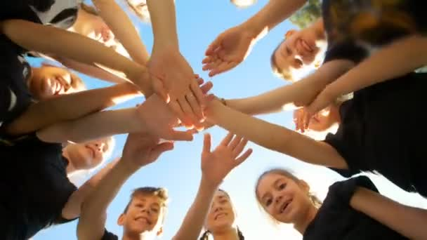 Group of school kids performs sports motivational greeting with hands on playground of yard football at sunny day