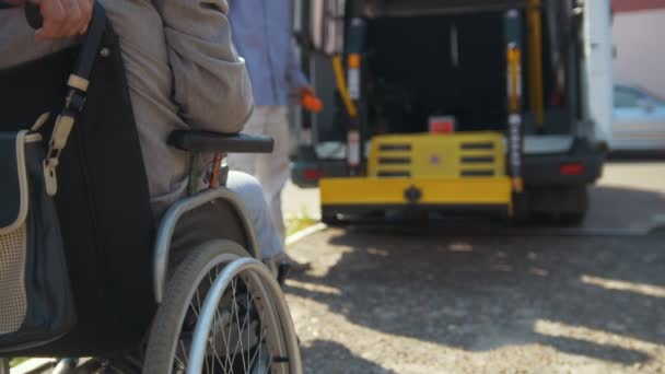 Lifting equipment for people with disabilities - man in wheelchair near the vehicle