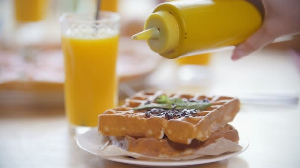 Female hands pours topping for waffles in restaurant