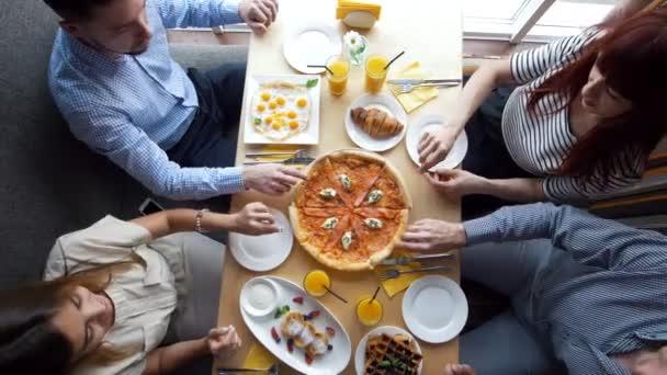 Mladí přátelé, přičemž pizza řezy z desky na stůl v restauraci