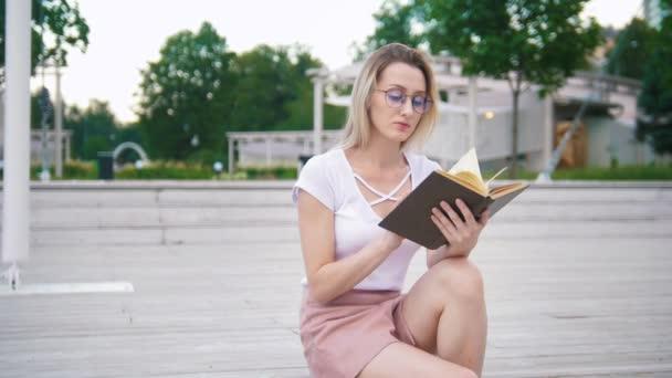 Mladá atraktivní žena v brýlích čte knihu posezení v parku