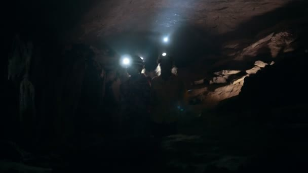 Three teenagers in helmets examines the dark cave with lanterns, wide angle