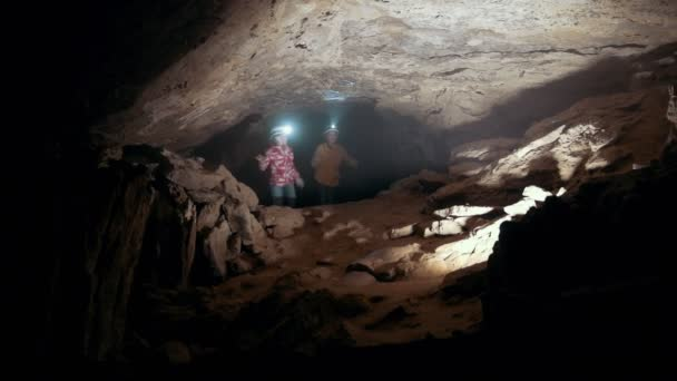 Three teenagers in helmets examines the dark cave with lanterns