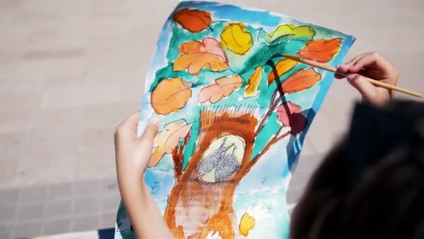 Little girl makes watercolor painting outdoors