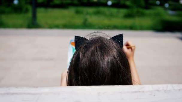 Pohled zezadu na malá dívka malba akvarelem sedí na lavičce v parku
