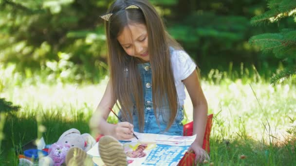 Cheerful little girl painting pictures with gouache on the grass in sunny day
