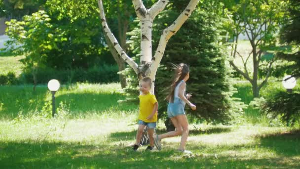 Cute girl with little brother having fun running around the tree outdoors at sunny day