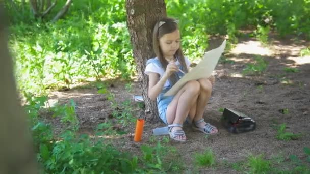 Little caucasian girl drawing with brush sitting under the tree at summer