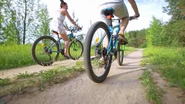Pohled zezadu na mladý pár, jízda na kole lesem letní