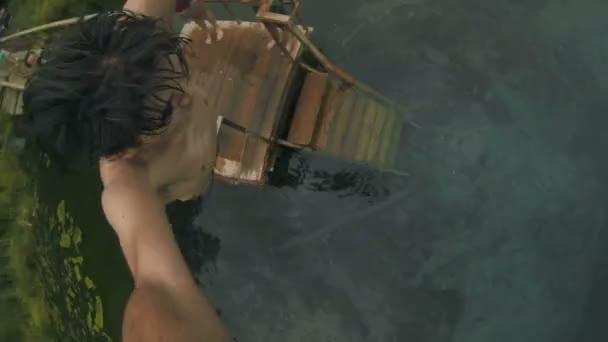 Mladý muž skočí z mola do jasné modré jezero
