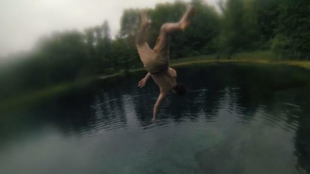 Mladý muž dělá zadní flip od mola do jasné modré jezero