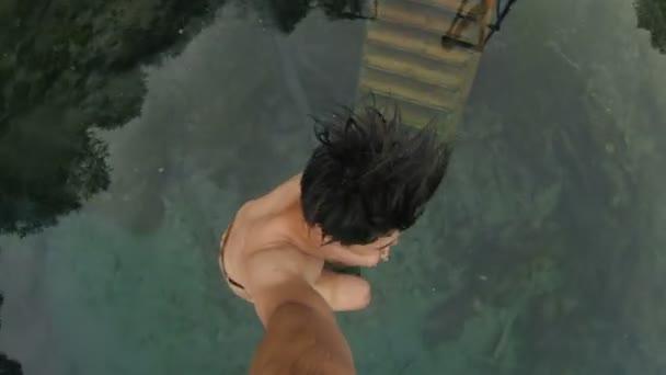 Mladý muž dělá skok z mola do jasné jezero