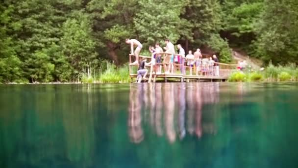 Young man jumping in the deep blue lake - de focused