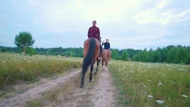 Női lovas lovaglás halad az úton a hátulnézet