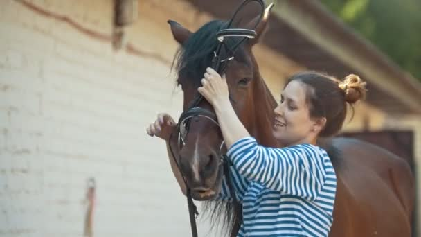 Happy young woman wears bridle for black horse in stable