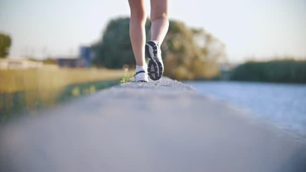 Sportovní dívka procházky v blízkosti řeky v teniskách