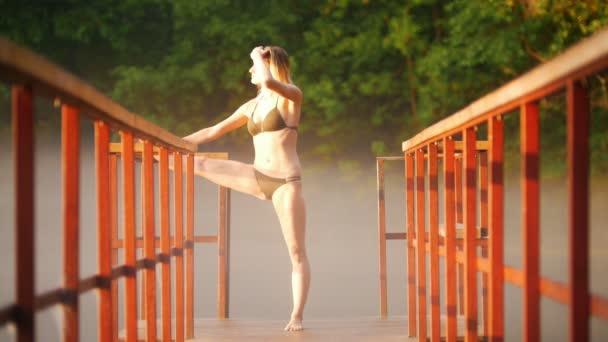 Mladá žena, která dělá teplé před plaváním nedaleko jezera, na mostě