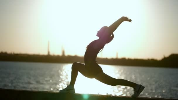 Amazing Silhouette Of A Girl Who Trains At The Water At Sunset